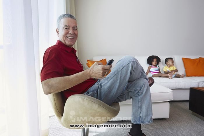 Grandfather relaxing with grandchildren in living room,