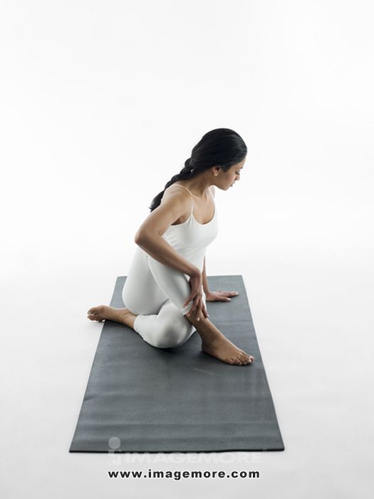 Woman practicing yoga on mat,