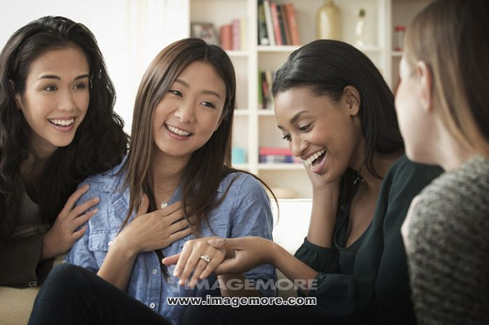 Woman showing engagement ring to friends on sofa,