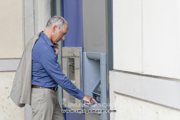 Caucasian businessman using ATM,