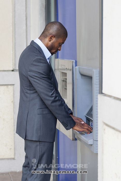 Black businessman using ATM in city,