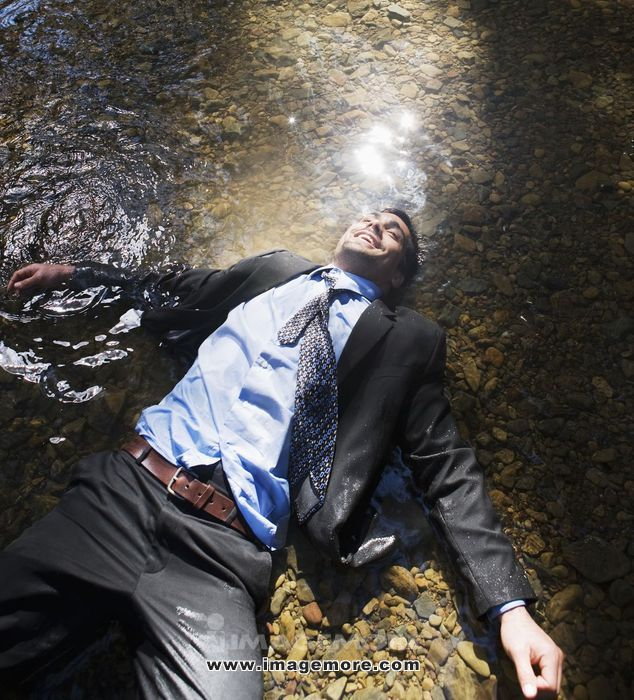 Hispanic businessman laying in water