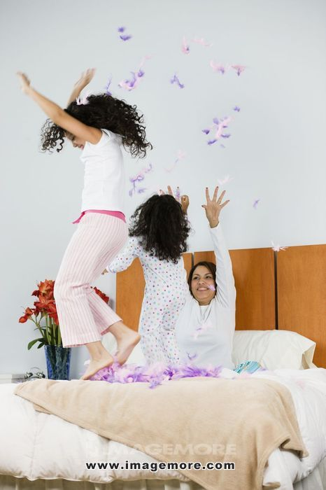 Hispanic mother and daughters throwing feathers in bedroom