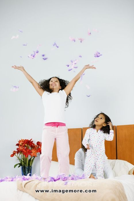 Hispanic sisters throwing feathers in bedroom