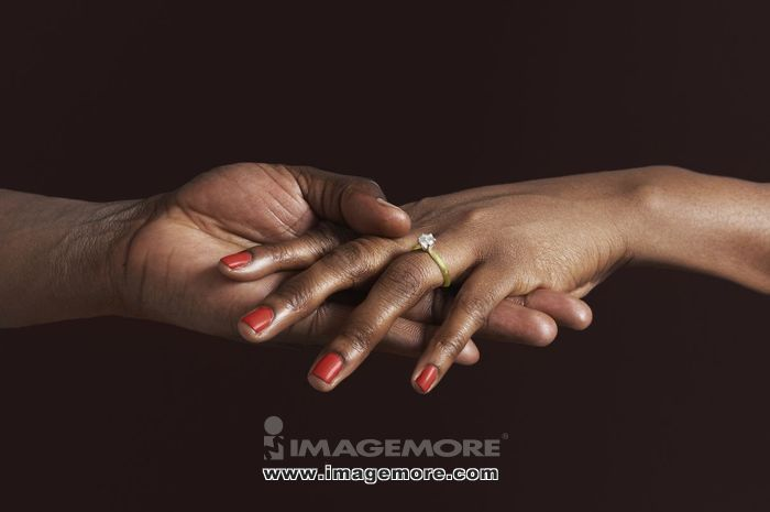 African woman with engagement ring holding fiancee's hand