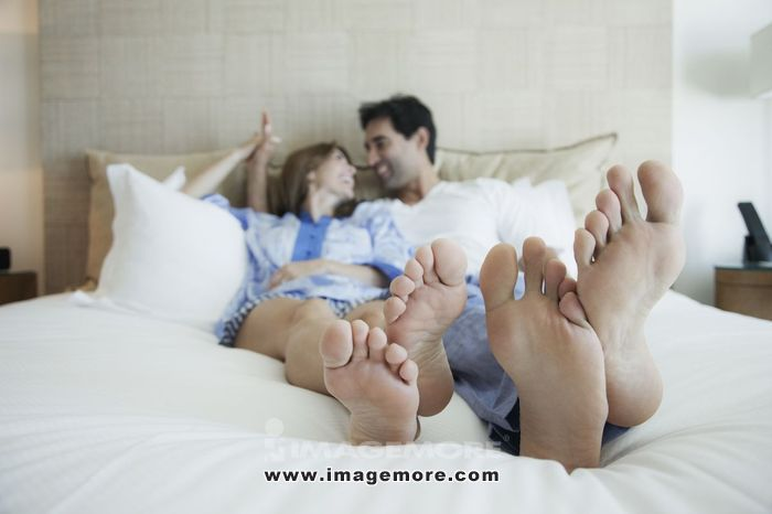 Hispanic couple laying on bed with bare feet