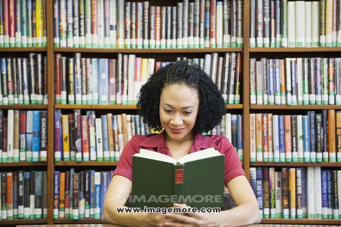 African woman reading book in library