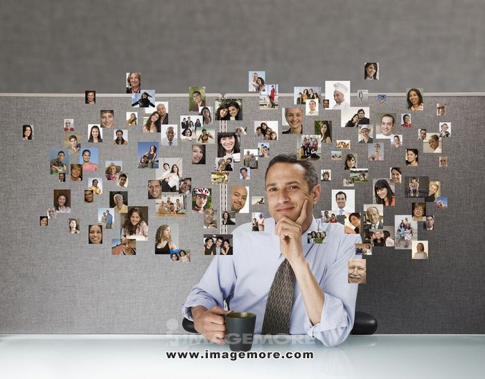 Businessman surrounded by pictures of family, friends and co-workers