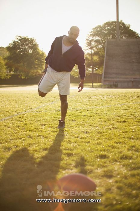 Man stretching on football field