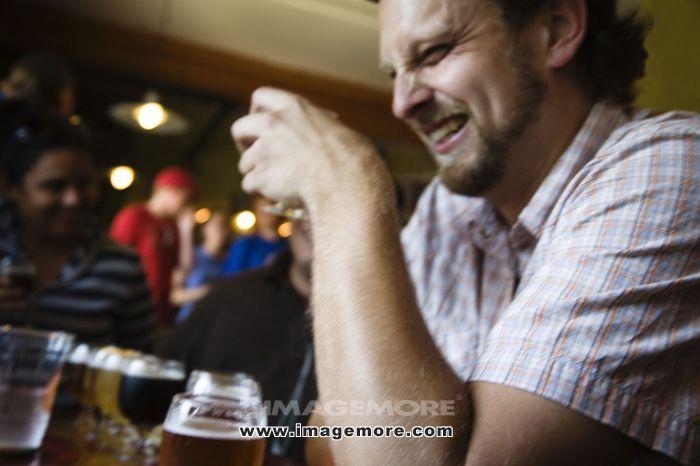 Caucasian man drinking in bar