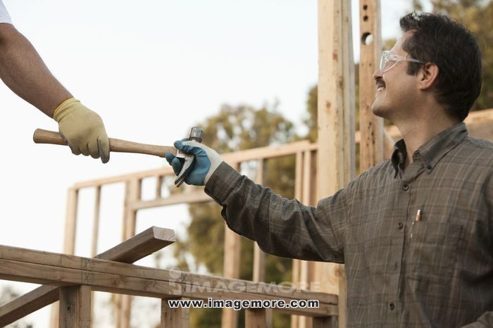 Co-worker handing mixed race construction worker a hammer