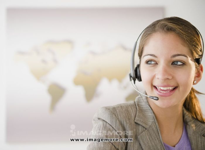 Indian businesswoman talking on headset in office