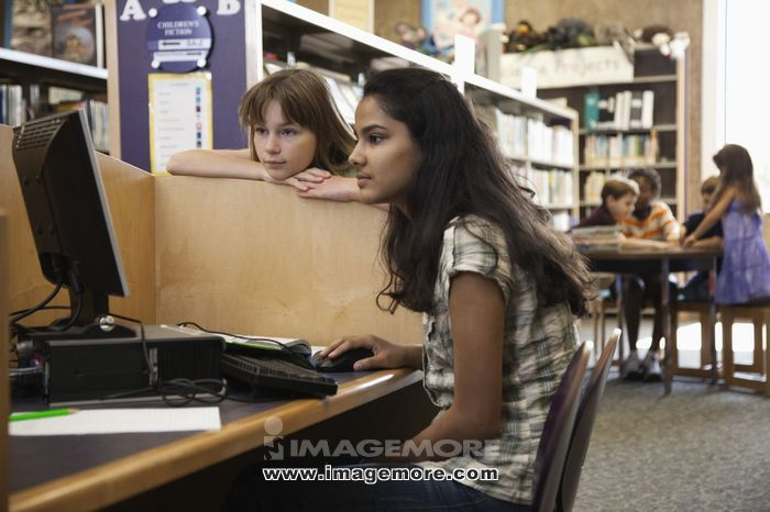 Children using computer in library together
