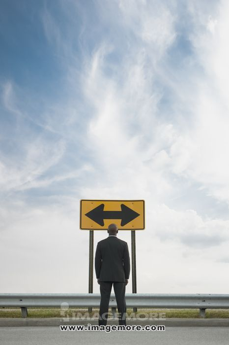 African American businessman looking at conflicting road sign