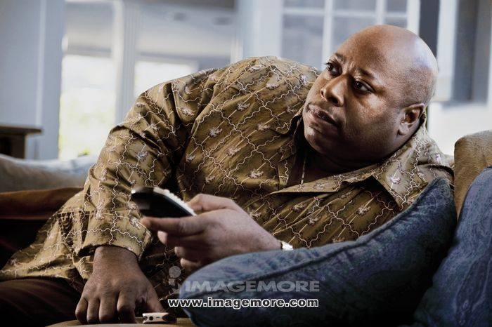 Black man reclining on sofa watching television