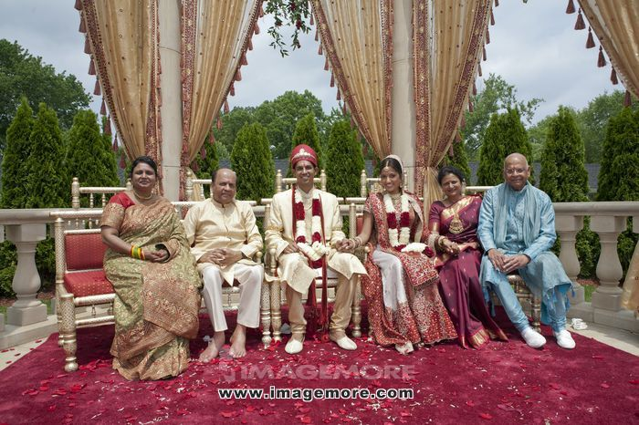 Indian bride and groom with family in traditional clothing