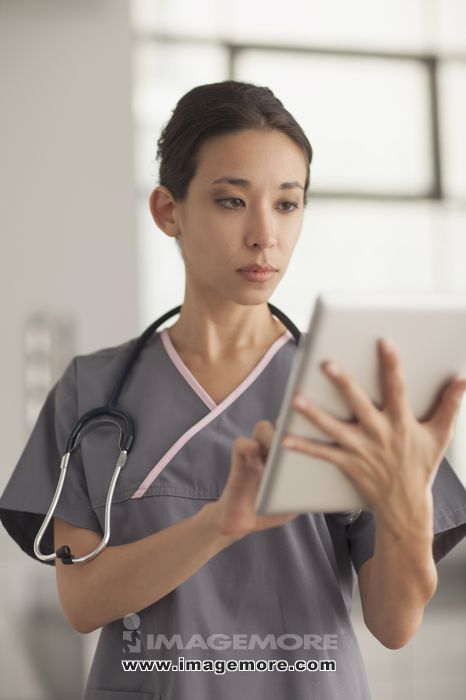 Mixed race nurse using digital tablet
