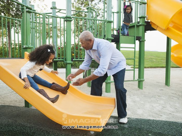 Man playing with granddaughter at park