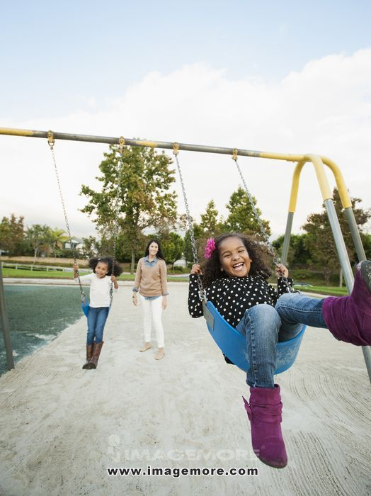 Mother pushing daughters on swings