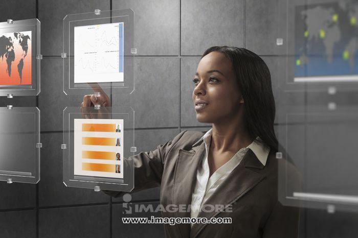 Mixed race businesswoman using touchscreen