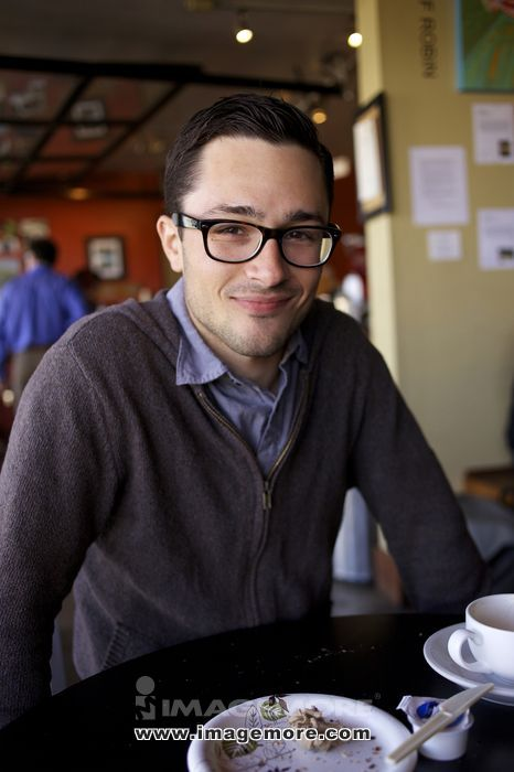 Man smiling at table in cafe