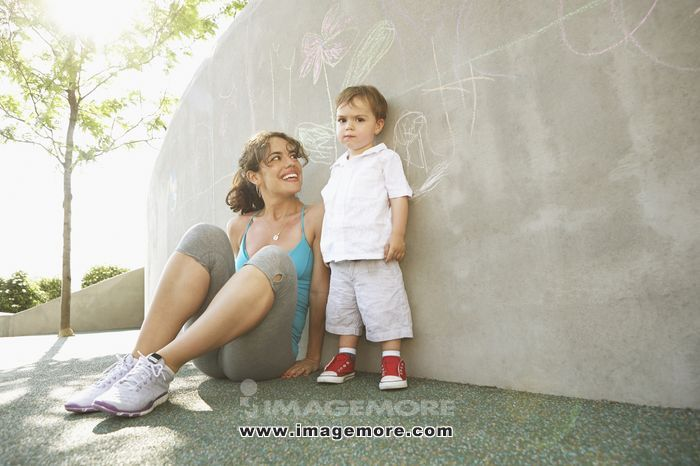 Mixed race mother sitting with son outdoors