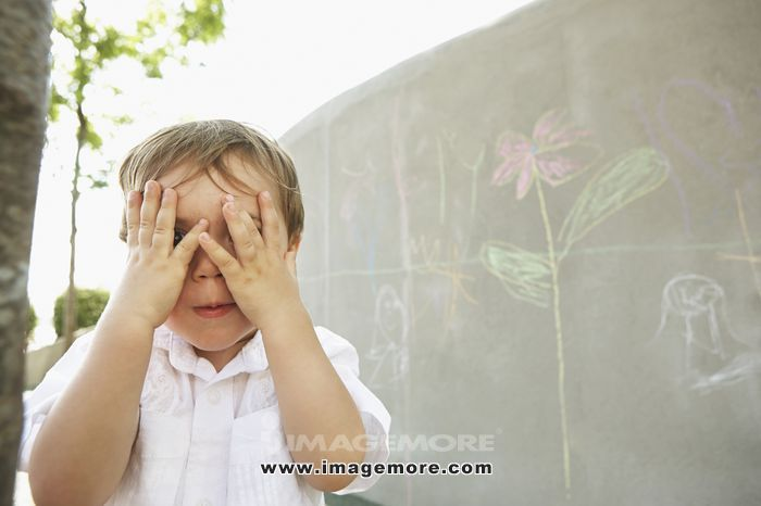Mixed race boy covering his eyes outdoors