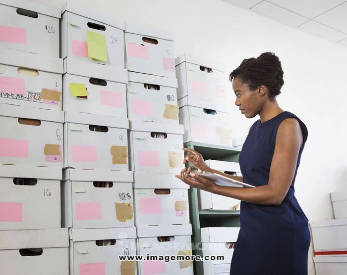 African American businesswoman searching for files in office