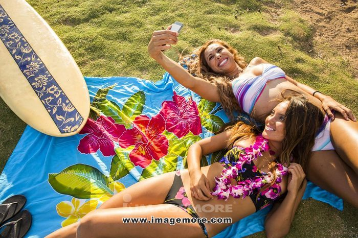 Women taking cell phone photograph together on blanket