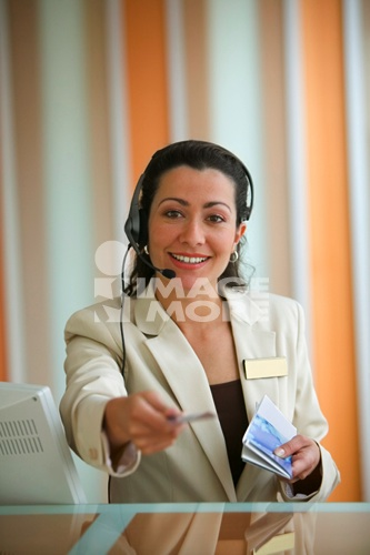 Woman travel agent holding tickets