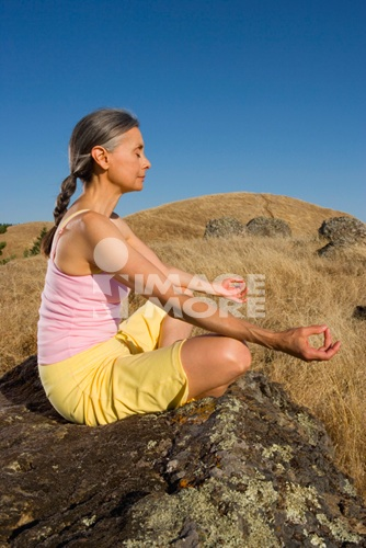 Senior woman meditating on a rock