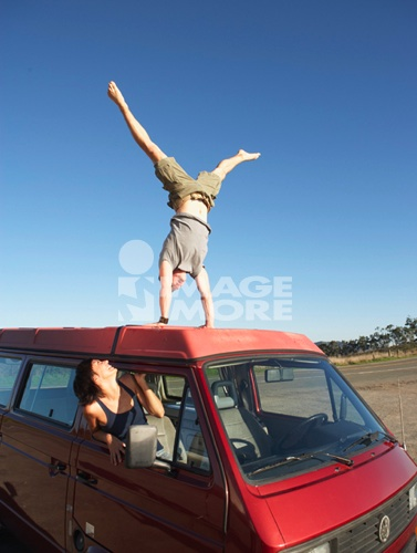 Man doing a handstand on car roof