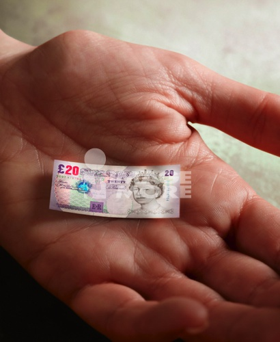 Man's hand holding tiny British Pound