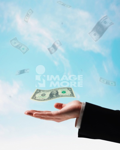 US Dollars floating in air above businessman's hand