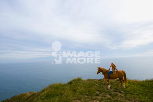 Senior woman horse riding bareback on cliff