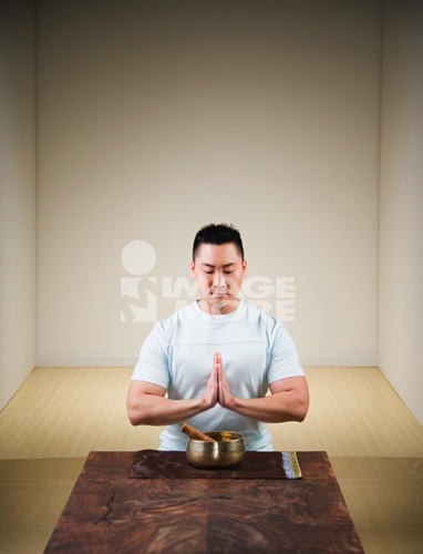Praying Asian man with singing bowl
