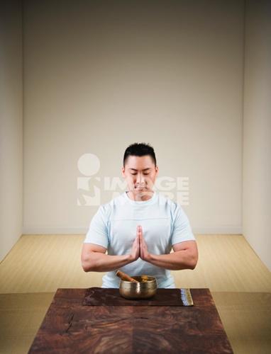 Praying Asian man with singing bowl
