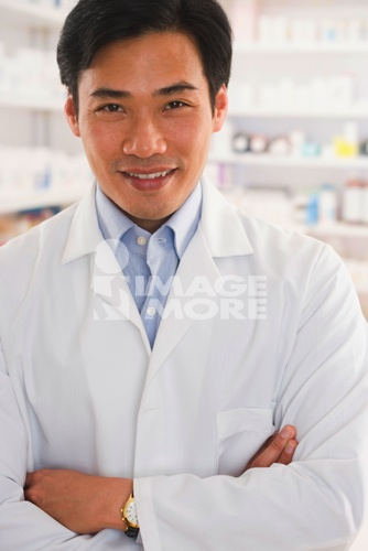 Asian male pharmacist standing in pharmacy