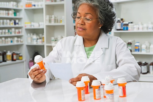 African female pharmacist reading medication label