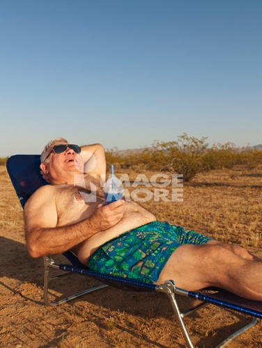 Senior Mixed Race man sunbathing in desert