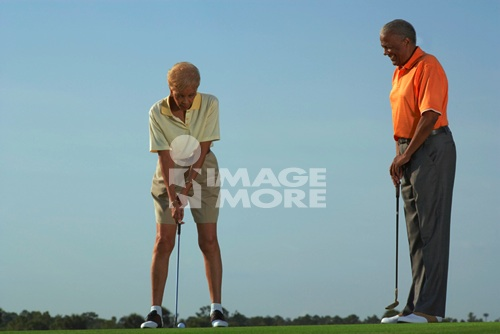 Senior African American couple playing golf