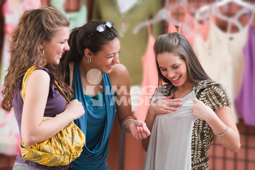 Multi-ethnic teenaged girls clothes shopping