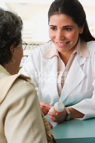 Hispanic female pharmacist discussing medication with customer