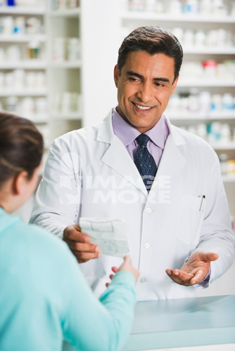 Hispanic male pharmacist handing prescription to customer