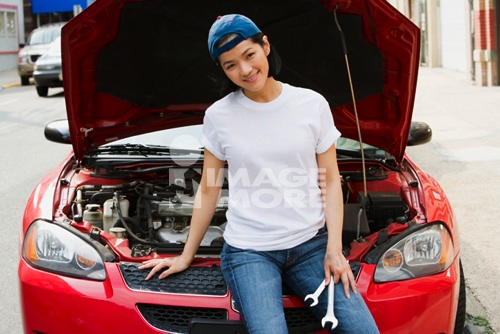 Asian woman holding wrenches next to open car hood
