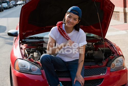 Asian woman sitting next to open car hood