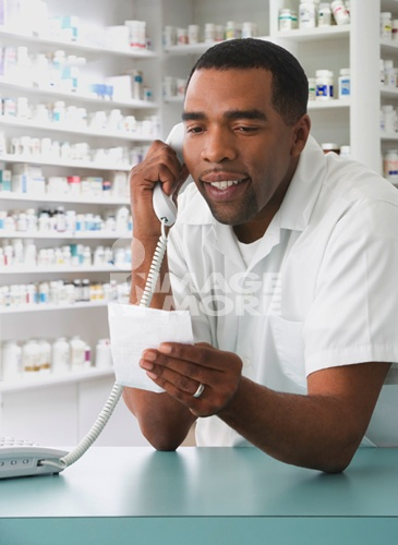 Mixed Race male pharmacist talking on telephone