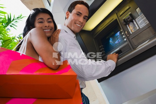 Hispanic couple using atm