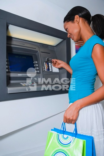 Hispanic woman using atm