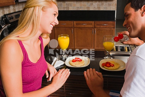 Hispanic couple eating breakfast